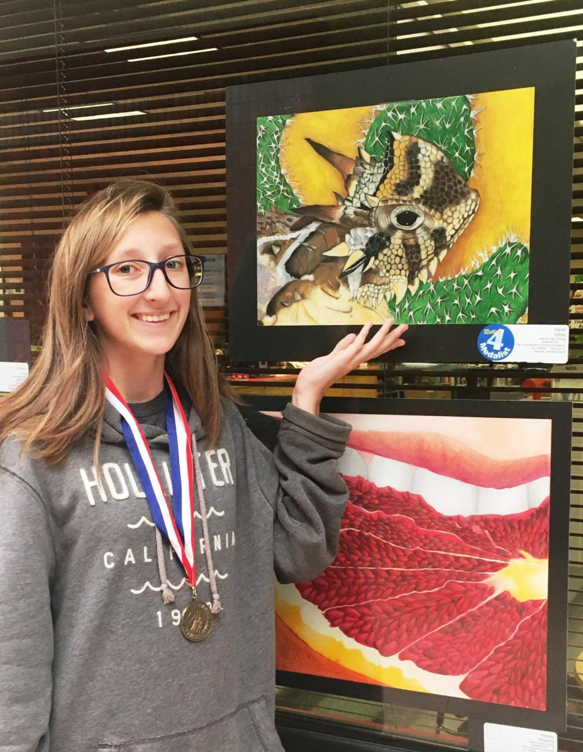 Sarah Webb displays her winning art piece. Webb placed first at the State VASE competition.