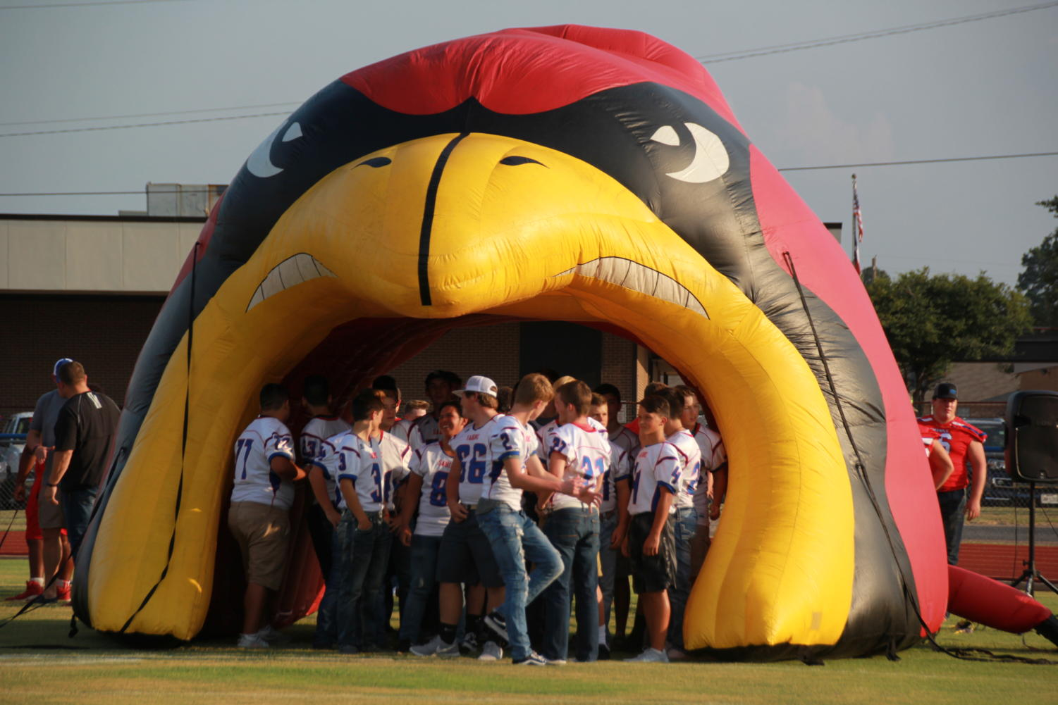 Football players gather in the helmet as they wait to be introduced.