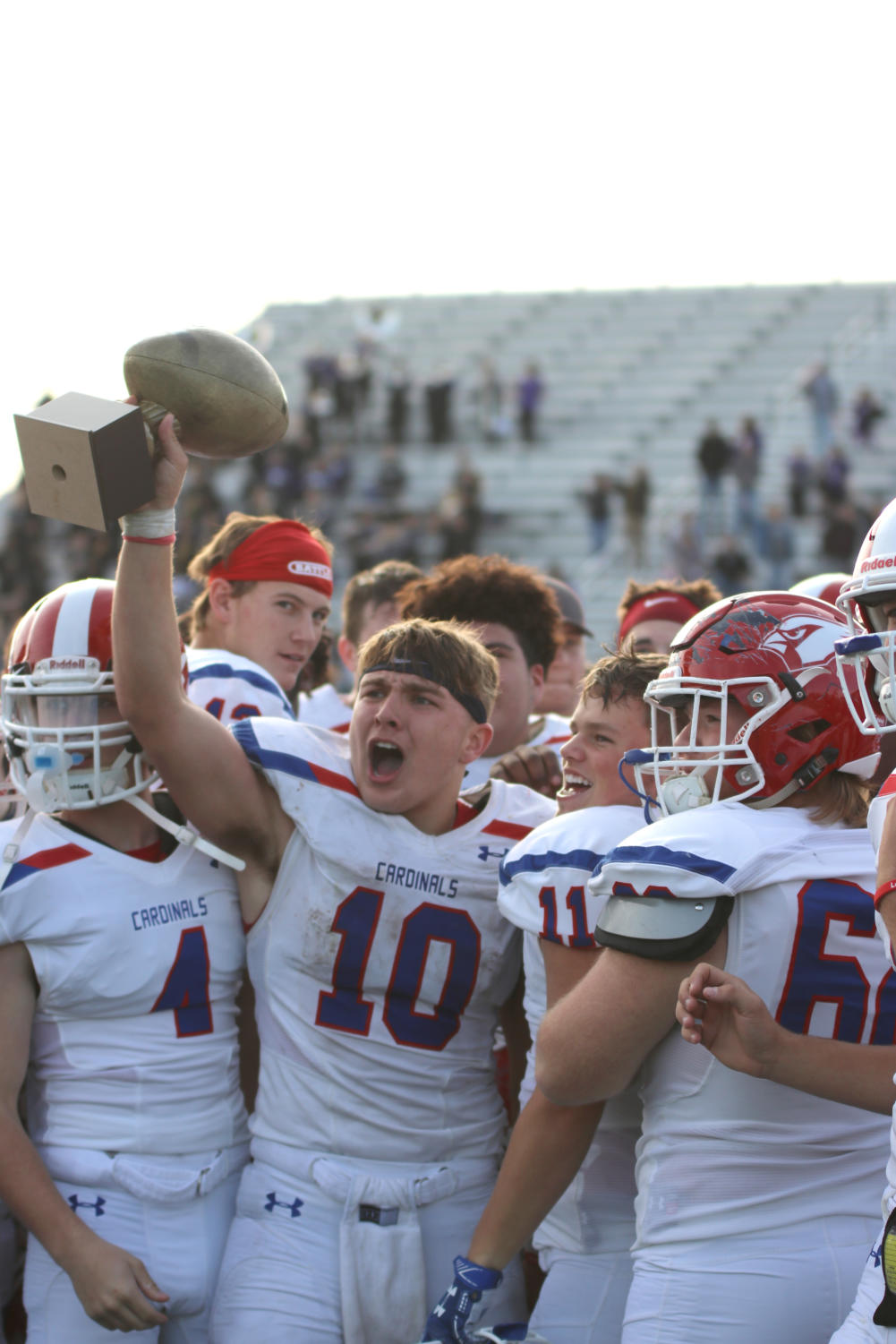 Senior Landon McKinney #10 holds up the bi-district trophy after winning the first playoff game.