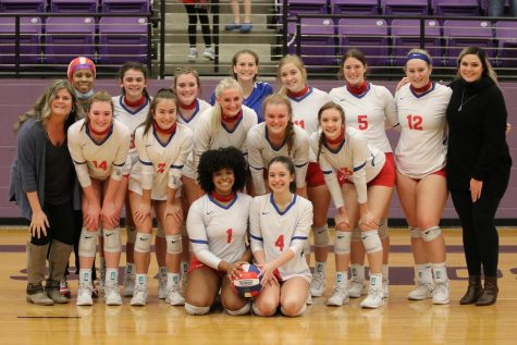 The volleyball team smiles for a group photo after winning the regional quarterfinal game against Tatum Nov. 5. The Cardinals beat the Eagles 3-0 to advance to the next round of playoffs.