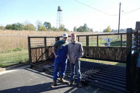 Seniors Sonny Whalen and Caden Loveless pose for a picture in front a cattle guard they, along with senior Coltin Reed (not pictured), worked on.