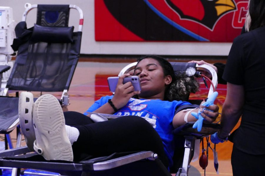 During the annual blood drive, junior Tayla Calico looks at her phone while giving blood in the gym Sept. 29.